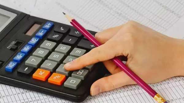 Рука на калькуляторе с карандашом