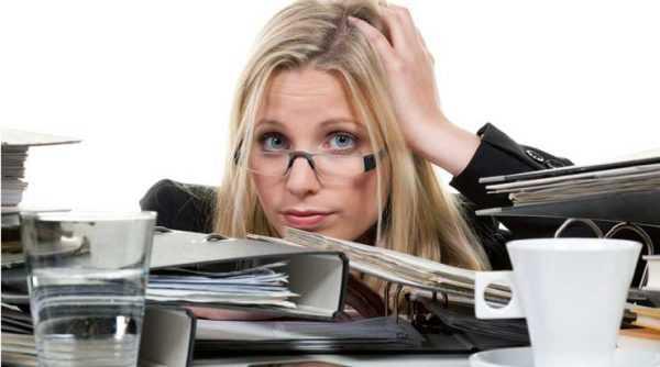 Светловолосая девушка держится за голову около кипы документов