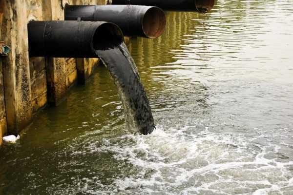 Вода вытекает из трубы в водоём