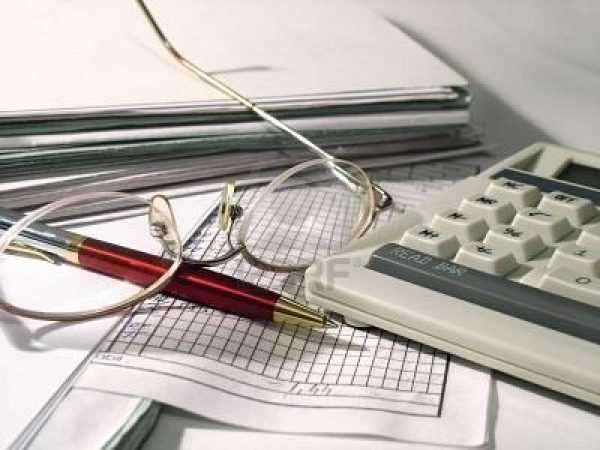 Очки, ручка, клавиатура на фоне документов