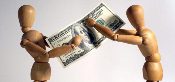 Два деревянных человечка делят долларовую купюру