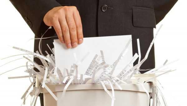 Мужская рука держит бумагу, которую измельчает шредер
