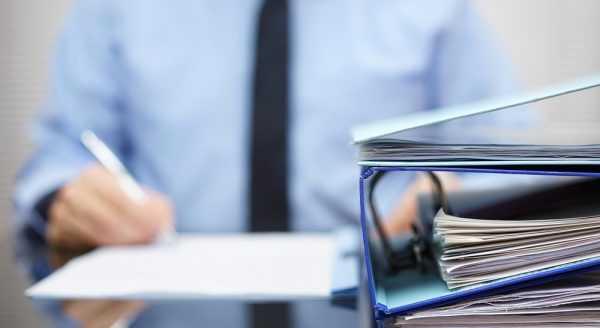 Папки с документами на фоне мужчины