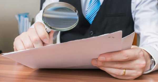 Мужчина рассматривает документ через лупу