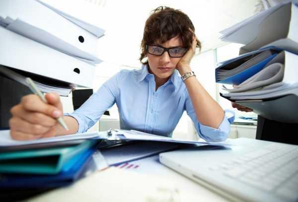 Женщина за рабочим столом заполняет документы