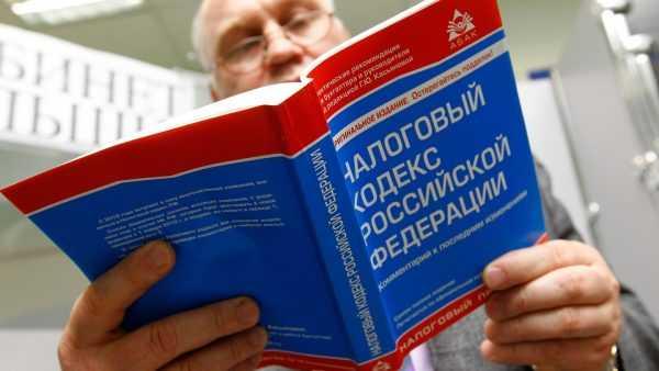 Мужчина держит Налоговый кодекс РФ