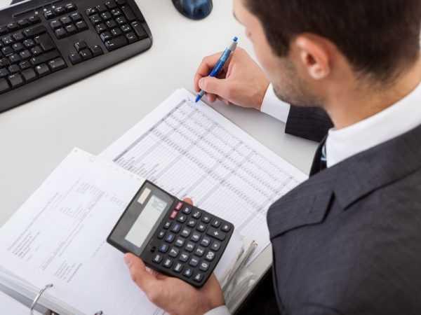 Мужчиначто-то пишет в документах и считает на калькуляторе
