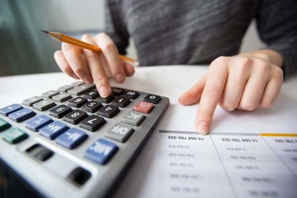 Девушка с карандашом в руке что-то считает на калькуляторе