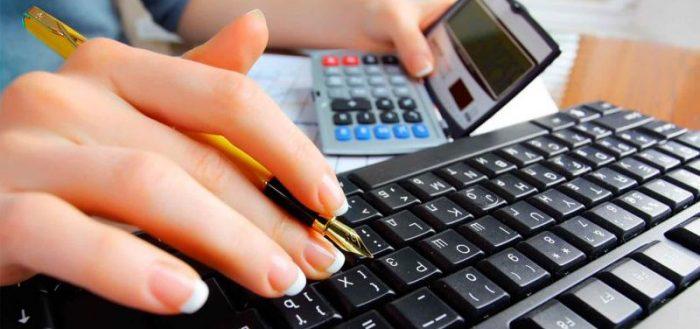 Женская рука, клавиатура компьютера и калькулятор