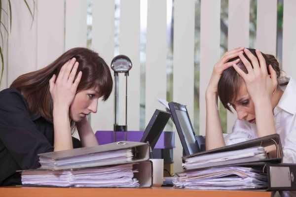 Папки с документами на столе и две женщины хватаются за головы
