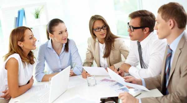Люди в офисе за столом с бумагами и ноутбуком