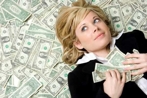 Молодая девушка лежит на денежных купюрах