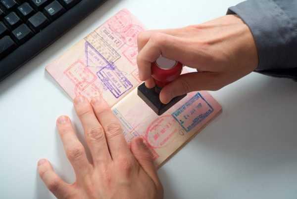Пограничник ставит тамп в паспорт