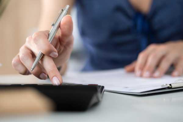 Человек с ручкой в руке считает на калькуляторе