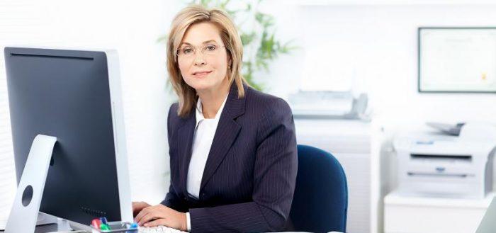 Женщина в офисной одежде за компьютером