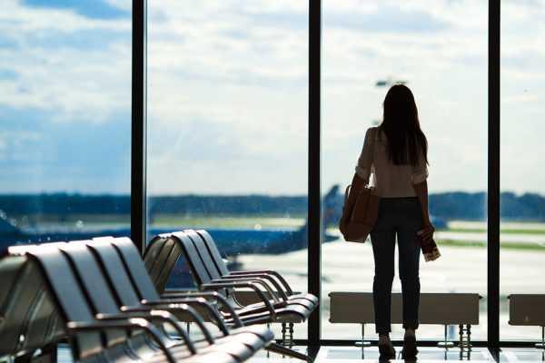 Женщина в аэропорту смотрит в окно