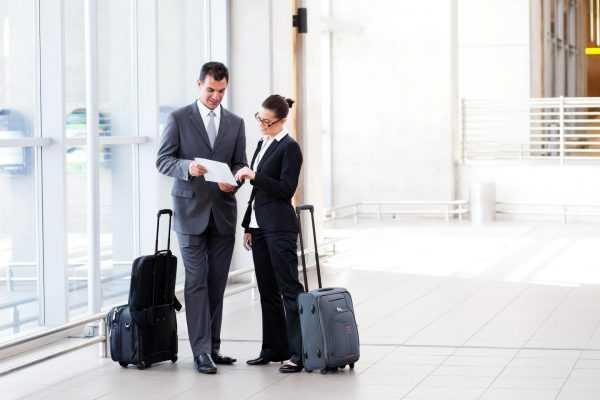 Мужчина и женщина с чемоданами рассматривают документ