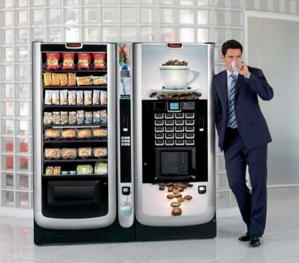 Вендинговые автоматы, рядом с которыми мужчина пьёт из стакана