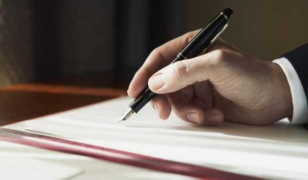 Крупным планом рука мужчины, заполняющего документ