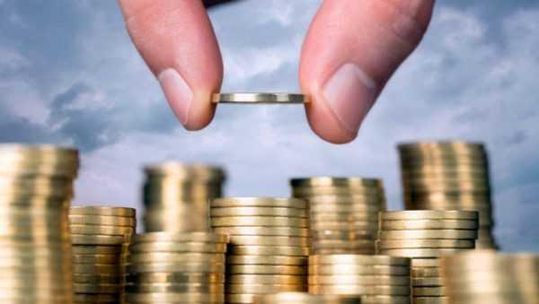 Стопки монет и пальцы, держащие монету