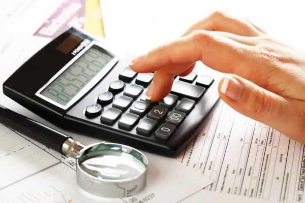 Рука на калькуляторе на фоне бумаг
