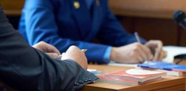 Руки мужчины и сотрудника ФНС, сложенные на рабочем столе