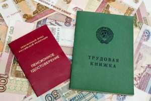Трудовая книжка и пенсионное удостоверение на фоне купюр