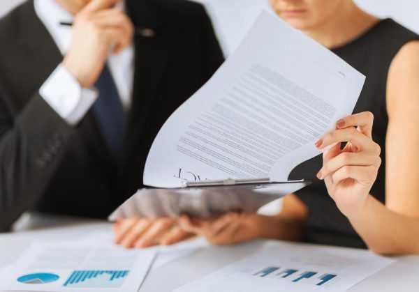 Женщина за столом в присутствии мужчины в костюме изучает документы