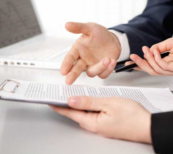 Два человека держат в руках деловые бумаги