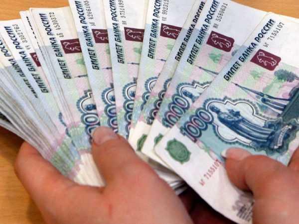 Купюры по тысяче рублей в руках у человека