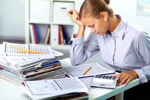 Женщина с калькулятором сидит над бумагами, задумавшись