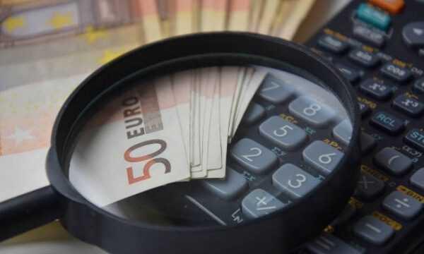 На калькуляторе лежат лупа и наличность в евро