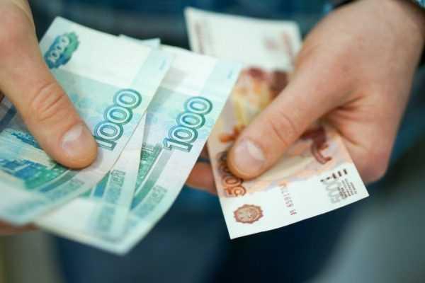 Крупные рублёвые купюры в руках
