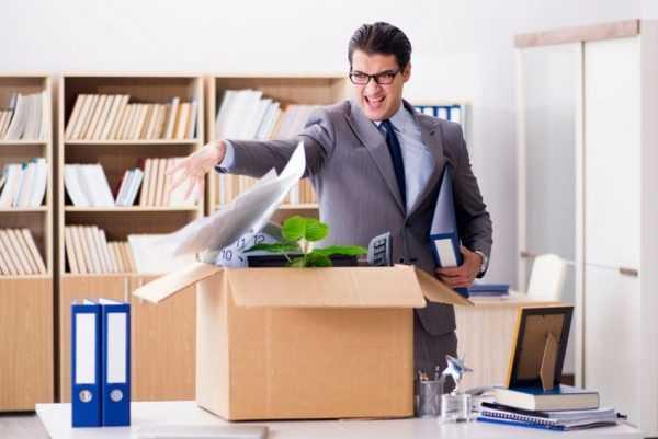 Недовольный офисный работник стоит над коробкой с личными вещами