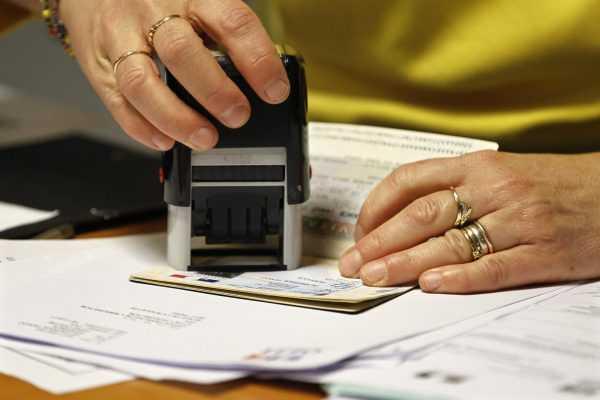 Руки, штампующие документы