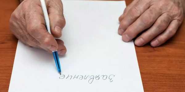 Пожилой человек пишет заявление