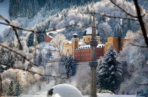 Зимний лес в Боснии на фоне замка и минарета