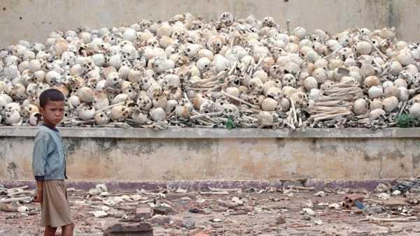 Камбоджийский мальчик на фоне человеческих костей
