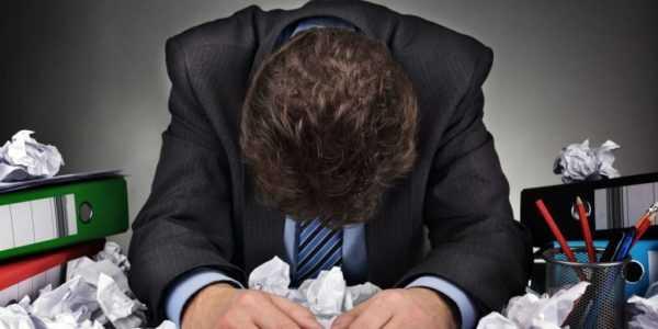 Человек в костюме за столом, заваленном мятыми бумагами