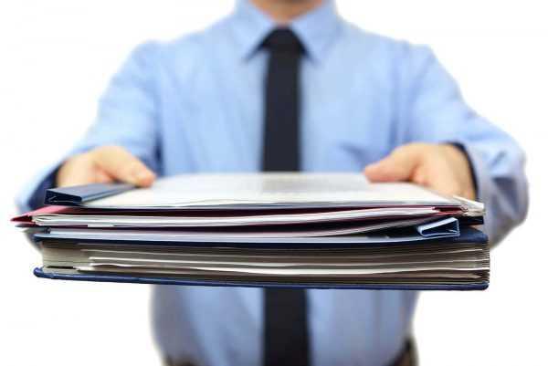 Человек в галстуке протягивает документы