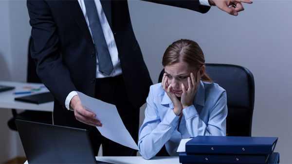 Человек в костюме показывает испуганной девушке бумагу