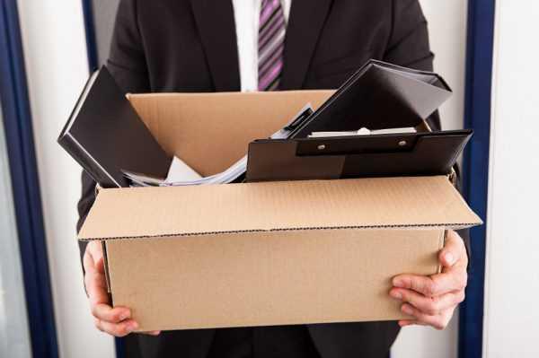 Мужчина несёт коробку с папками и бумагами