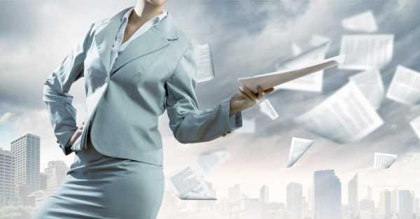 Женщина в деловом костюме швыряет в воздух бумаги