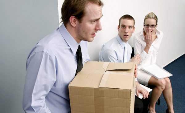 Молодой человек с коробкой покидает помещение, другие с ужасом смотрят на это