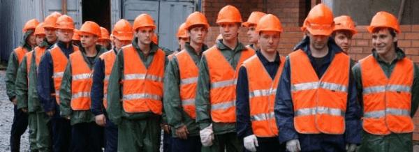 Очередь из молодых строителей в касках и жилетах