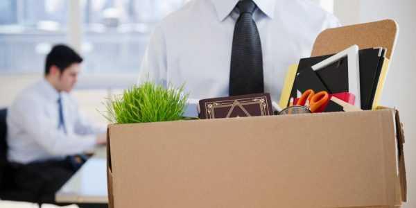 Мужчина в галстуке несёт коробку с рабочими вещами, фото и цветком