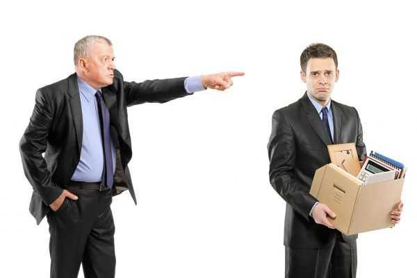 Возрастной человек в костюме указывает на дверь молодому, стоящему с коробкой, куда сложена рабочая канцелярия