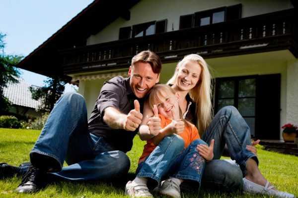 Мама, папа и дочка сидят на траве у частного дома