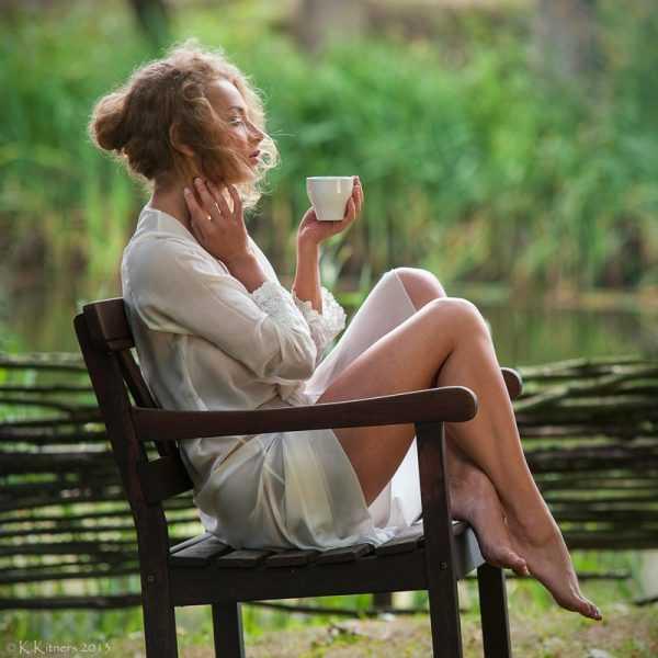 Женщина сидит с чашкой на стуле у плетня