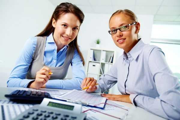 Девушки за столом с бымагами и калькулятором